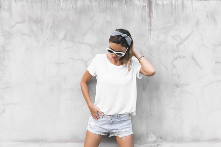 Photo pour Hipster girl wearing blank white t-shirt and denim shorts posing against gray street wall, blank mockup for tshirt print store - image libre de droit