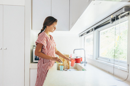 Photo pour Teenage girl washing dish in the modern white kitchen. 12 years old girl doing housework. - image libre de droit