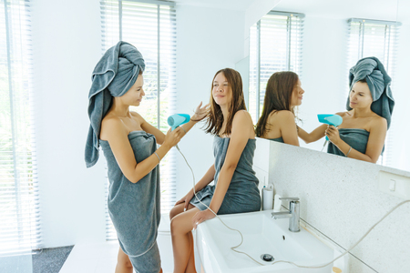 Foto de Mom with teenage dauhter making everyday routine in modern hotel bathroom together. Mother is brushing and drying child hair after shower. - Imagen libre de derechos