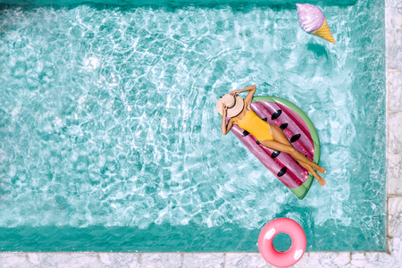 Photo pour Woman relaxing on watermelon lilo in the pool at private villa. Inflatable ring and mattress. Summer holiday idyllic. High view from above. - image libre de droit