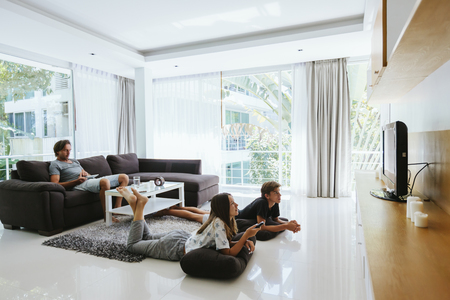 Photo pour Two teenagers watching tv while relaxing on couch in living room - image libre de droit