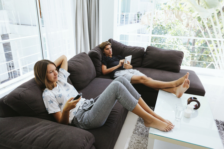 Foto de Two teenagers using ipad and watching tv while relaxing on couch in living room - Imagen libre de derechos