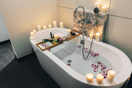 Photo pour Prepared luxury spa bath decorated with flowers and candles, with wooden tray on it - image libre de droit