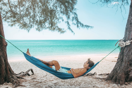 Photo for Teenage boy chilling in hammock under the shade of a tree on tropical beach , hot sunny day - Royalty Free Image