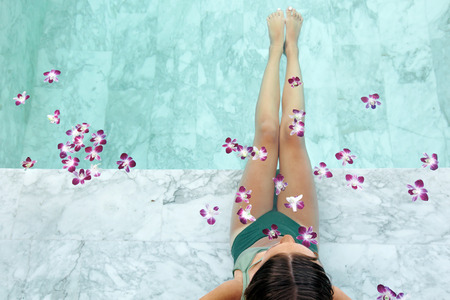 Photo for Girl relaxing in tropical spa pool decorated with flowers in luxury hotel. - Royalty Free Image