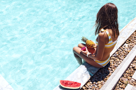 Photo pour Girl sitting by pool and eating vegan food, POV photo of legs closeup. Tropical fruit diet. Summer holiday idyllic concept top view. - image libre de droit