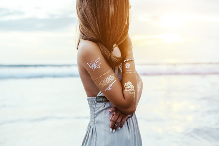 Photo pour Young teenage girl with silver tattoo and boho jewelry over shore on sunset - image libre de droit