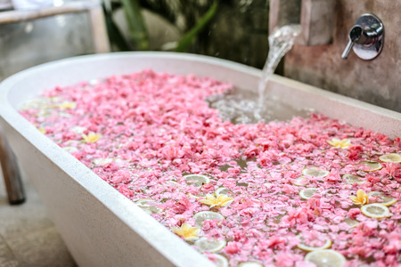 Photo pour Bath tub filling with water with flowers and lemon slices. Organic spa relaxation in luxury Bali outdoor bathroom. - image libre de droit