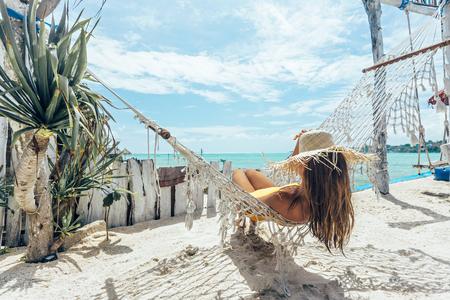 Photo pour Girl relaxing in hammock in tropical beach cafe, hot sunny day at paradise island - image libre de droit