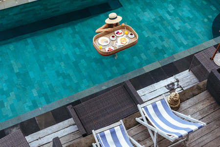 Photo pour Girl relaxing and eating in luxury hotel pool. Served floating breakfast in tropical Bali resort. - image libre de droit