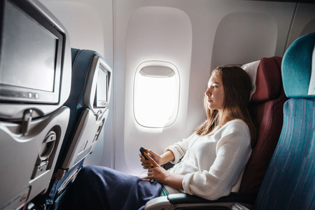 Photo pour Teenage girl using media on board during flight. Young passenger travelling by airplane by first time. - image libre de droit