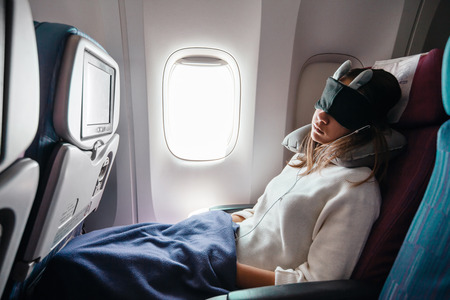 Photo pour Teenage girl sleeping on boad during flight. Young passenger travelling by airplane alone. - image libre de droit