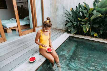 Photo pour Girl relaxing and eating watermelon in the pool on luxury villa in Bali. Exotic summer diet. Tropical beach lifestyle. - image libre de droit