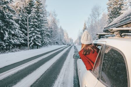 Foto de Rear view of teen girl in car over snowy forest on winter roadtrip to the nordic way - Imagen libre de derechos