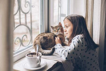 Photo pour Child in pajamas relaxing on a window sill with pet. Lazy weekend with cat at home. Cozy scene, hygge concept. - image libre de droit