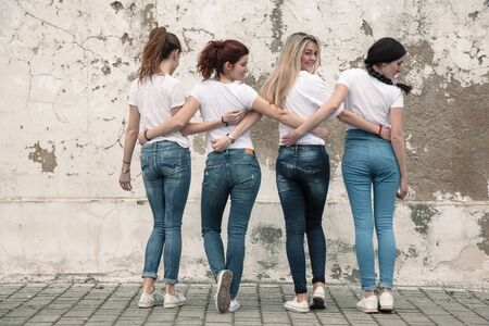 Photo pour Group of four young diverse girls wearing blank white tshirt and jeans posing against rough street wall, fashion urban clothing style, mockup for t-shirt print store - image libre de droit