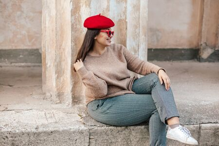 Photo pour Plus size fashion model wearing simple sweater, red beret and chic sunglasses posing in the old city street in autumn. Stylish fall clothing for beautiful and happy overweight woman. - image libre de droit