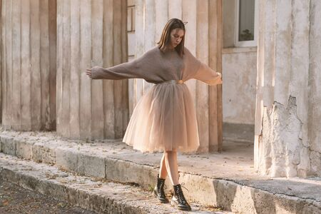 Sepia filtered photo of teen girl wearing brown tulle skirt, knitted oversized sweater and leather boots posing in city street.