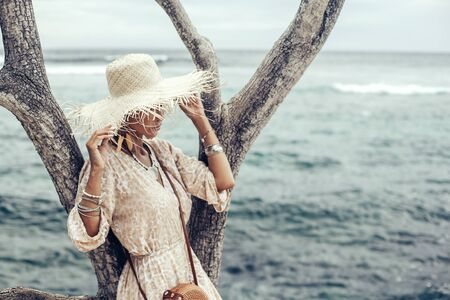 Photo pour Boho styled model wearing dress, straw hat and bag on the beach in Bali - image libre de droit