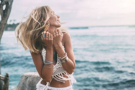 Photo pour Boho styled model wearing white crochet crop top with tassels and silver jewelry on the beach - image libre de droit
