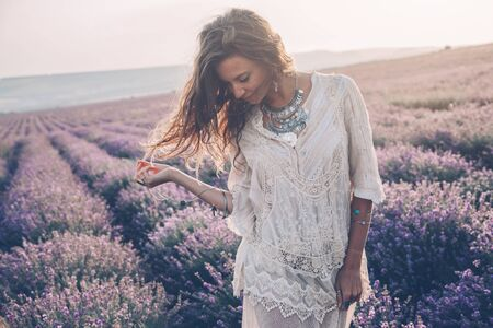 Photo pour Beautiful model walking in spring or summer lavender field in sunrise sunshine. Boho style clothing and silver jewelry. - image libre de droit
