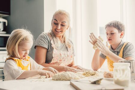 Photo for Beautiful blond mom teaching her two children cooking on the kitchen. Parent making everyday breakfast together with kids. Family at home lifestyle photo. - Royalty Free Image