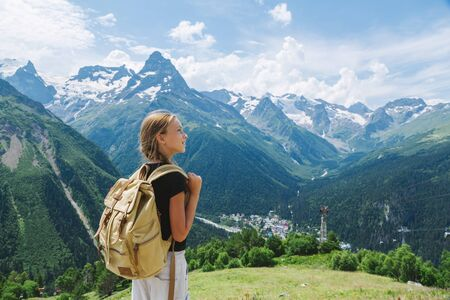 Photo for Child girl traveler with backpack standing on mountain hill and enjoying amazing summer view. - Royalty Free Image