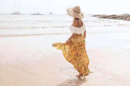 Photo pour Girl wearing floral maxi skirt walking barefoot on the sea shore, Thailand, Phuket. Bohemian clothing style. - image libre de droit
