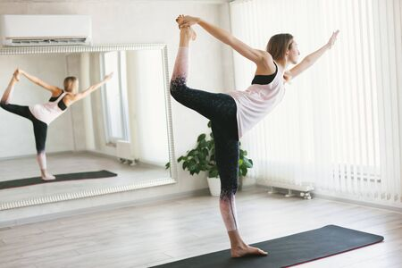 Foto de Young woman doing stretching exercise by mirror on floor mat in bright yoga class room. - Imagen libre de derechos