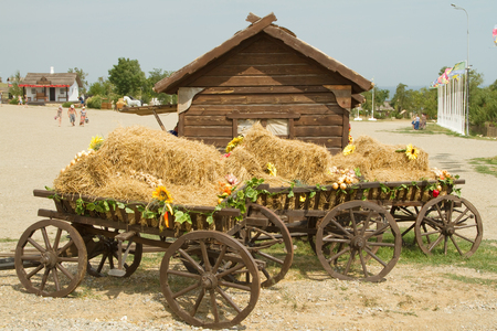 TAMAN, RUSSIA - AUGUST 12: Old wooden cart with straw in the ethnographic village Ataman on August 12, 2015 in Taman.