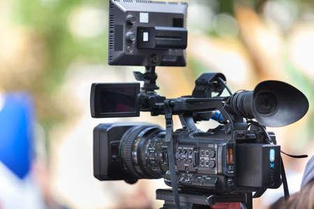 Photo pour Man journalist with a modern large black video camera on bokeh background - image libre de droit