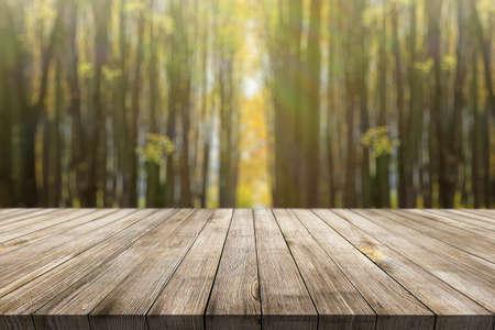 Photo pour Wooden desk on autumn blur natural background - image libre de droit