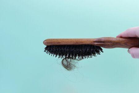 Photo pour Fallen hair and a wooden comb. Copy space - concept of health problems, treatment, baldness, serious illness - image libre de droit