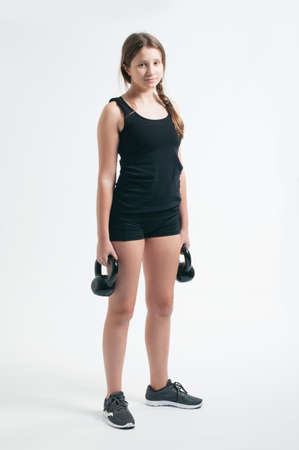 Photo for teenage girl during the squat with the kettlebells over the white background - Royalty Free Image