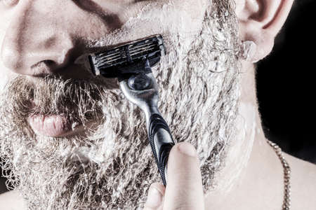 man in shaving foam shaves his beard and mustaches with a razor, photo close-upの写真素材