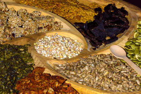 a plateau of oriental sunflower seeds and nuts in a wooden tray background image