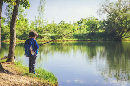 Photo pour Little kid play with stick looks like rod and fishing on the lake in the forest on a sunny day. - image libre de droit