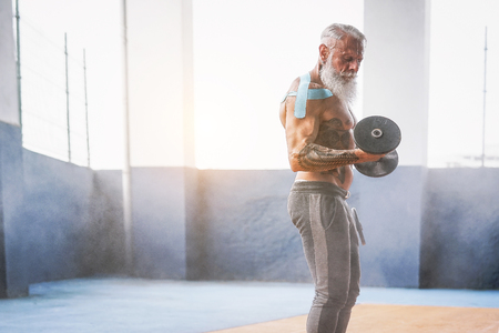 Foto de Fitness beard man doing biceps curl exercise  inside a gym - Tattoo senior man training with dumbbells in wellness club center - Body building and sport fit concept - Imagen libre de derechos