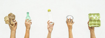 Foto de Human hands holding recyclable objects as paper, glass, plastic, aluminium on a white background - Eco concept with recycling - Focus on hands - Imagen libre de derechos