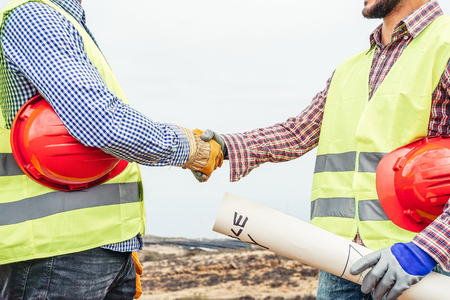 Photo pour Builders shaking hands making an agreement on costruction site - Workers reaching a deal on renewable energy project on the working site - Building, dealing, engineer industrial concept - image libre de droit
