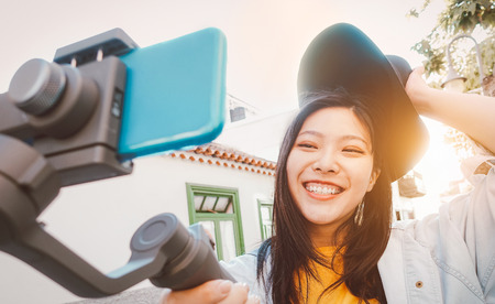 Photo pour Asian woman making video with smartphone gimbal outdoor - Happy Asiatic girl having fun with new technology trends for social media - Millennials people, generation z, tech and youth lifestyle concept - image libre de droit