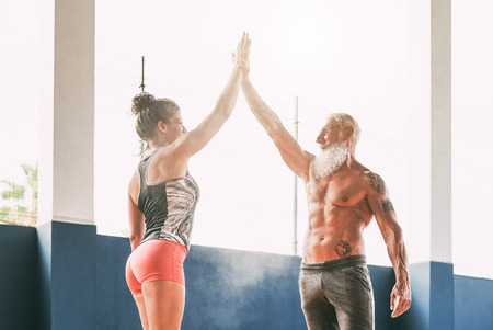 Foto per Fitness couple stacking hands in gym wellness club - Happy athletes motivating each other - Concept of people training, fit, empowering and bodybuilding lifestyle - Immagine Royalty Free