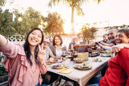 Photo pour Happy family cheering and toasting with red wine glasses at dinner outdoor - People with different ages and ethnicity  having fun at bbq party - food and drink, retired and young people concept - image libre de droit