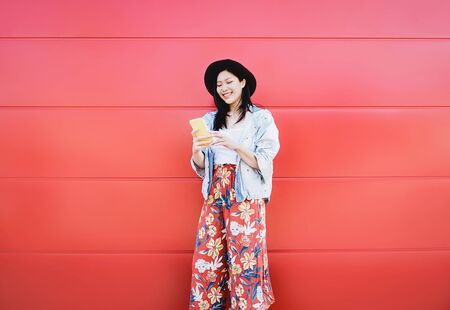 Foto de Happy Asian girl using mobile phone outdoor - Chinese social influencer having fun with new trends smartphone apps - Generation z, media, technology and youth millennial people lifestyle - Imagen libre de derechos