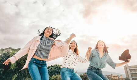 Photo for Happy Asian girls jumping outdoor - Young women friends having fun during university break - Millennial generation, friendship and youth people lifestyle - Royalty Free Image