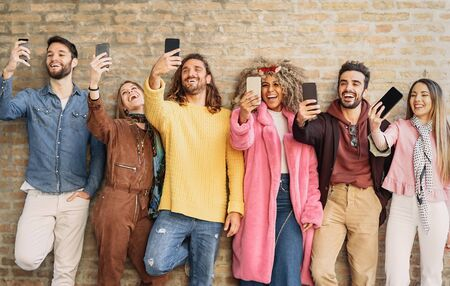 Photo for Happy group friends taking selfie with cell phone outdoor - Young trendy people having fun with new mobile smartphone apps for social media - Youth culture millennial generation and Technology concept - Royalty Free Image