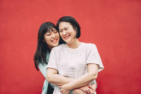Foto de Happy Asian mother and daughter having fun outdoor - Chinese family people spending time together outside - Love, relationship and parenthood lifestyle concept - Imagen libre de derechos
