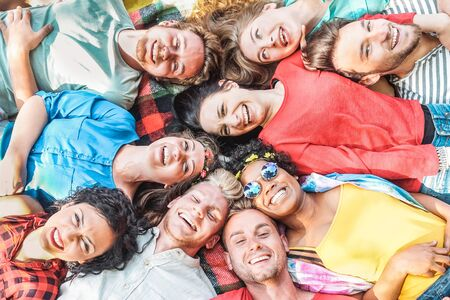 Photo pour Group of diverse friends having fun outdoor - Happy young people lying on grass after picnic and laughing together - Friendship, unity, millennial and youth lifestyle concept - image libre de droit