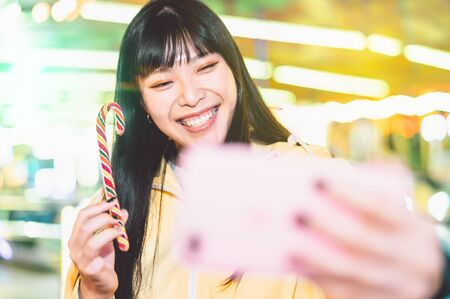 Photo for Asian girl taking selfie with mobile phone in amusement park - Happy  woman having fun with new trends smartphone apps - Youth millennial people generation and social media addiction concept - Royalty Free Image