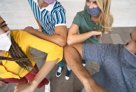 Foto de Young friends wearing face mask doing new social distancing greet with elbows bumps for preventing corona virus spread - Physical distance and friendship safety greetings concept - Imagen libre de derechos